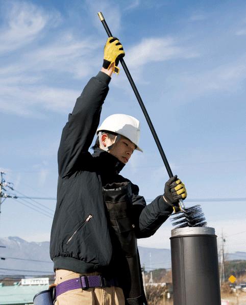 屋根に上って煙突内の煤を除去する